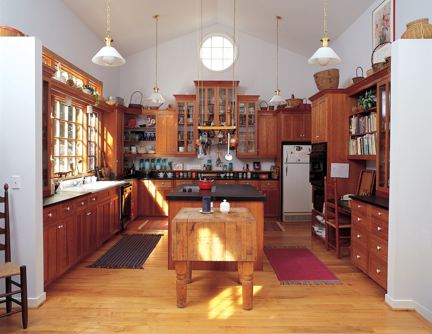 Cherry Kitchen with open shelves, display cabinets, pot rack, and chopping block.