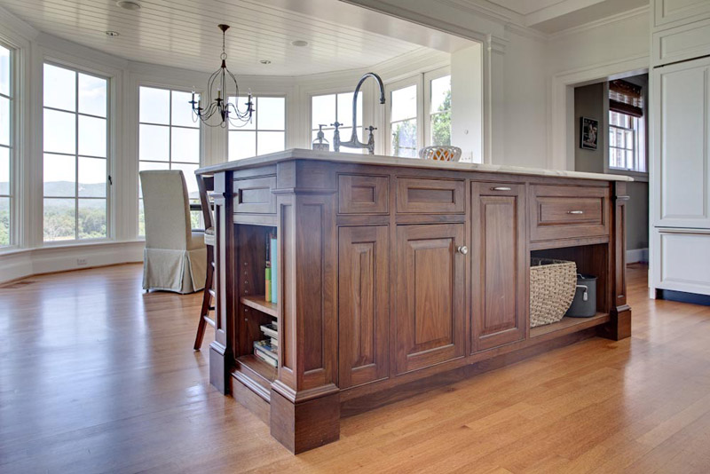 This walnut island has ample storage and display areas with seating on the far side.