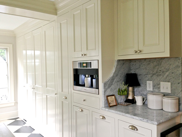 A run of storage cabinets and cupboards with a built in coffee maker.