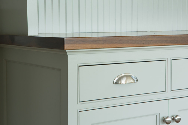 Detail of solid walnut counter and beaded door and drawer front openings.