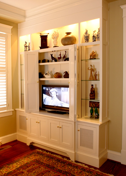 Glass shelves and lighting enhance this built-in which also houses a flat screen TV.