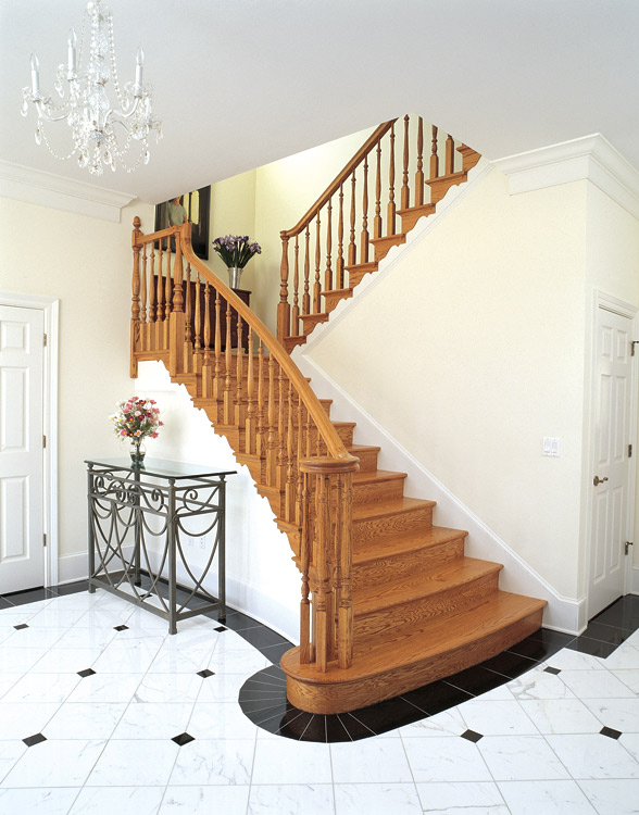 This formal oak stair flares at the bottom and has curving treads.