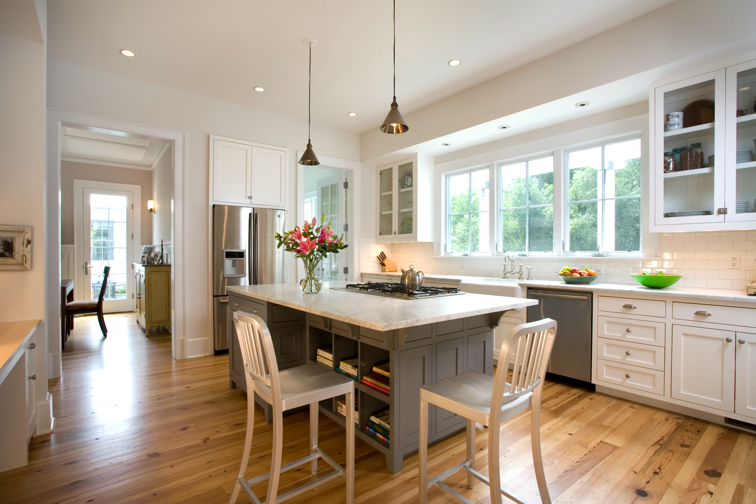 The kitchen features a farm sink and island cooktop with inset cabinet doors and drawer fronts.