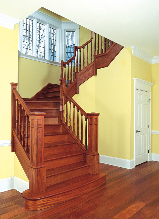This Brazilian cherry and mahogany stair fits in an angled bay. Cascading goose necks in the rail and custom newel posts add distinction.