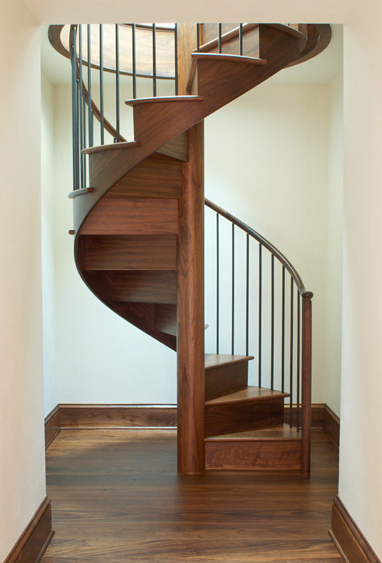 Walnut spiral stair with risers and skirt. The whole structure is knitted together and needs less robust anchoring to the post.