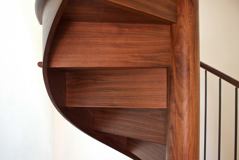 Walnut spiral stair with risers and skirt. Closeup of the underside.
